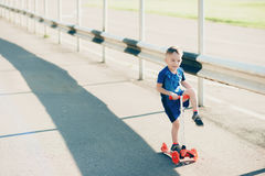 Little boy on a scooter in a city park, outdoors Royalty Free Stock Photos