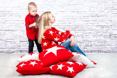 Little boy scratching his comb mom with long blond hair.Among the soft pillows for home interior decorating. Stock Photos