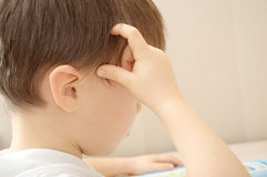 Little boy scratching his head Royalty Free Stock Photography