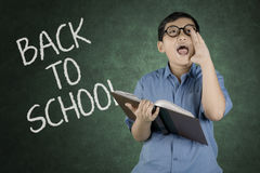 Little boy screaming in the classroom. Portrait of little boy screaming while holding a book with back to school text on the chalkboard in classroom Stock Photos