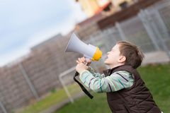 Little boy screaming through a megaphone. Outdoor Royalty Free Stock Photo