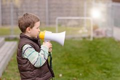 Little boy screaming through a megaphone Stock Image