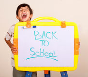 Little boy screaming with a whitebaord. With text back to school on it Stock Image