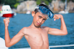 Little boy with scuba mask showing muscles. On sea Royalty Free Stock Images