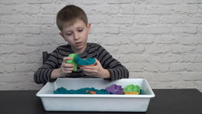 Little boy sculpting sand stock video footage