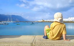 Little boy by the sea; Graciosa; Canaries. Two year old boy in yellow shirt and a sun hat watching harbor area in Caleta de Sebo, main harbor in Graciosa Island Stock Photos