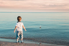 The little boy by the sea throws stones in water. Sunset. Happy childhood Stock Photo