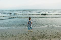 the little boy by the sea throws stones in water. sunset. Happy childhood royalty free stock images