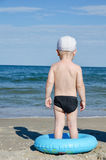 Little boy on the seashore with a swimming circle is with his back Royalty Free Stock Photo