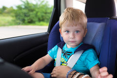 Little boy is seating in the car Stock Photos
