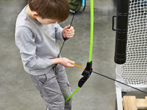 Little boy sets arrow in children`s sports bow Stock Photography