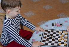 Little boy setting up a game of checkers Royalty Free Stock Photography