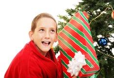 Little Boy Shaking Christmas Gift. Cute little boy shaking a Christmas gift to guess what's inside. White background stock photo