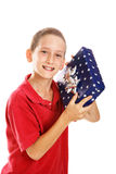 Little Boy Shaking Holiday Gift. Little boy shaking a gift. Wrapping could be for Hanukkah or Christmas. Motion blur on package. Isolated stock images