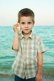 Little boy with a shell on the evening beach. Stock Images