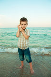 Little boy with a shell on the evening beach. Royalty Free Stock Photography