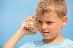 Little boy with shell listening noise of sea Stock Photography