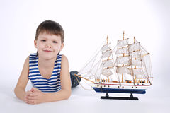 Little boy with ship on white Royalty Free Stock Image
