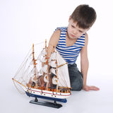 Little boy with ship on white Royalty Free Stock Photos