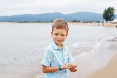 Little boy in shirt and shorts on the beach sand. Little boy hav. Ing fun on tropical ocean beach. Kid during family sea vacation. Summer water fun Stock Image