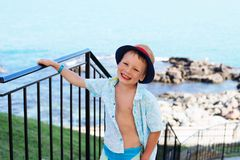 Little boy in shirt and shorts on the beach sand. Little boy hav Stock Image