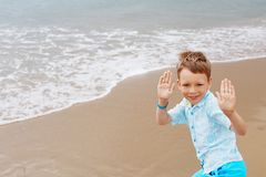 Little boy in shirt and shorts on the beach sand. Little boy hav Stock Images