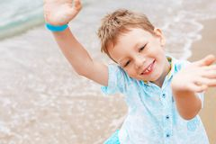 Little boy in shirt and shorts on the beach sand. Little boy hav Royalty Free Stock Image