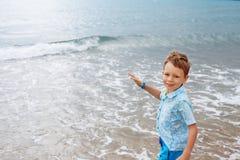Little boy in shirt and shorts on the beach sand. Little boy hav Stock Photo