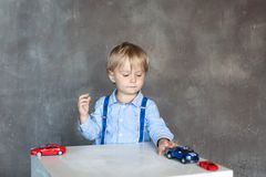 A little boy in a shirt with suspenders plays with toy multi colored toy cars. Preschool boy playing with toy car on a table at ho stock photography