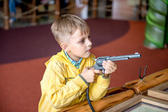 Little boy shooting by revolver in amusement park Stock Image
