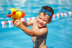 Little boy shooting with water gun Stock Photos