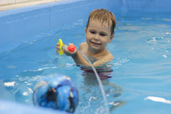Little boy shooting with water gun in the pool Royalty Free Stock Photography