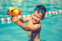 Little boy shooting with water gun in the pool vintage Royalty Free Stock Image