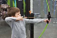 Little boy shoots by bow in children`s shooting range. Little boy shoots a bow in a children`s shooting range Royalty Free Stock Image