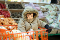 Little boy in shopping cart. Cute little boy sitting in shopping cart Stock Photo