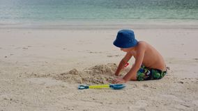 A child sits on the beach near the water and digs a hole with a shovel. stock footage