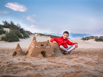 Little boy in shorts and a jacket sitting legs crossed near the sandy castle against the blue sky and the sand dunes Stock Images