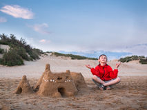 Little boy in shorts and a jacket sitting legs crossed near the sandy castle and meditates against the blue sky and the sand dunes Royalty Free Stock Images