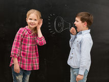Little boy shouting in drawn mouthpiece and girl covering ears with her hands. Little boy shouting in drawn on the blackboard mouthpiece and little girl covering Stock Photos