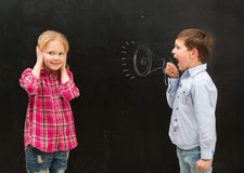 Little boy shouting in drawn mouthpiece and girl covering ears with her hands. Little boy shouting in drawn on the blackboard mouthpiece and little girl covering Stock Image