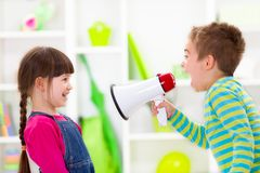 Little boy shouting loud to girl. Children playing communication - little boy shouting loud to girl Stock Photo
