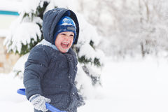 Little boy with shovel playing in snow Royalty Free Stock Photography