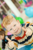 Little boy show thumbs up. Little boy lying on the floor surrounded by colorful balloons shows thumbs up Stock Images