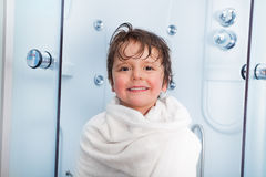 Little boy after shower covered in towel smile. Happy little 4 years old boy covered in warm white hotel towel getting out of shower cabin with big happy smile Stock Photo
