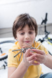 Little boy showing bicycle multi tool on white Stock Images