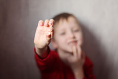 Little boy showing his first lost milk-tooth in his hand. Royalty Free Stock Image