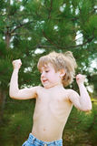 Little boy showing his muscles. A young boy flexing his muscles while playing outside Stock Image