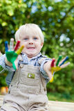 Little boy showing his painted hands outside. Young Caucasian child showing his colorful painted hands outdoors royalty free stock photo