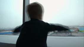 Little boy showing plane with hands looking at it stock video