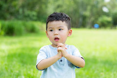 Little boy showing pray gesture. Asian young little boy at outdoor royalty free stock photo